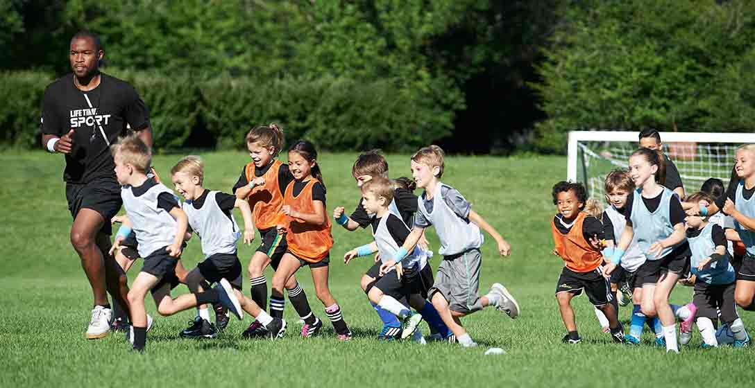 b8482c2c7c7 Male soccer coach runs on outdoor soccer field with young players in soccer  jerseys