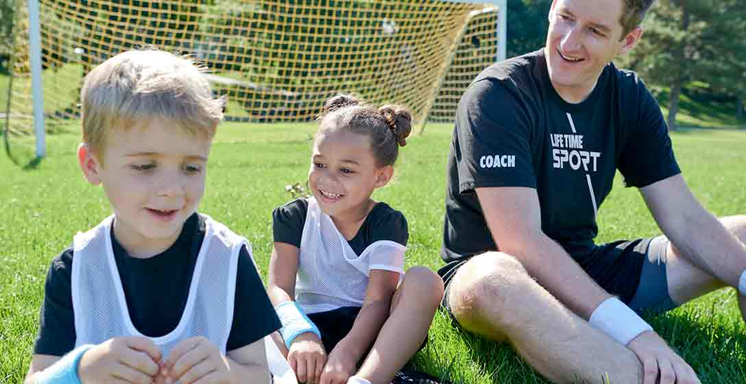 Male soccer coach sits on soccer field with a young girl and a young boy in soccer jerseys