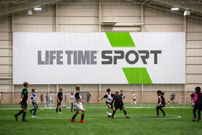 A group of youth soccer players play soccer on an indoor soccer field at the Life Time Sport at Winter Park