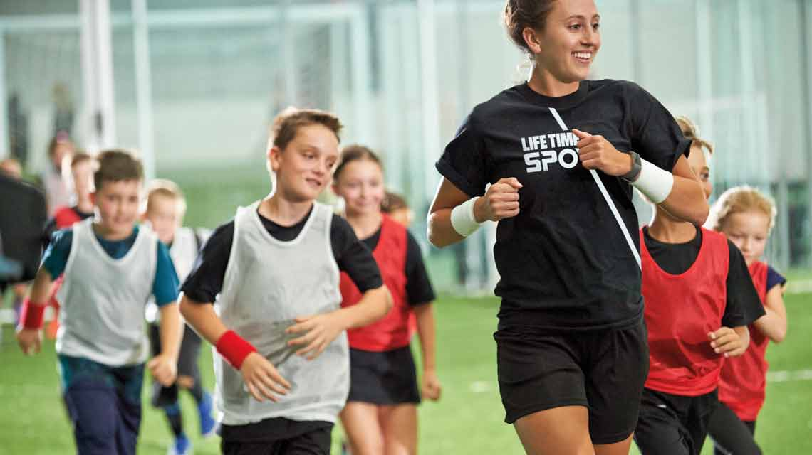 Female soccer coach runs with youth players in soccer jerseys on indoor field