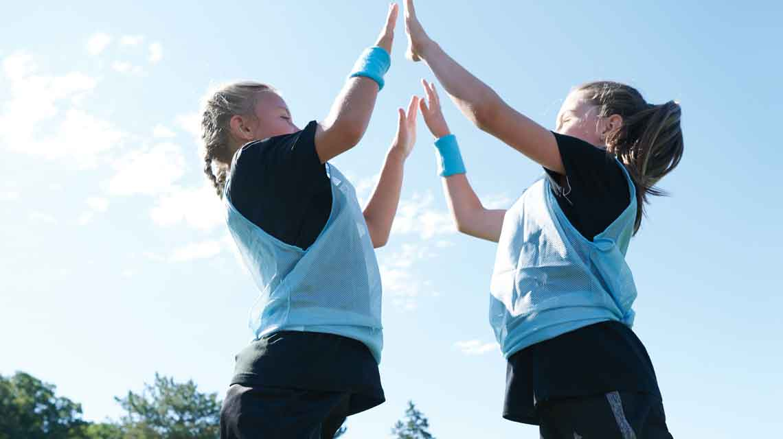 Two young girls in soccer jerseys double high five on outdoor soccer field