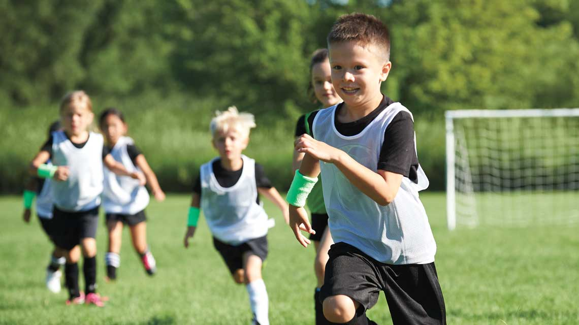 Young boys and girls in soccer jerseys run on outdoor soccer field