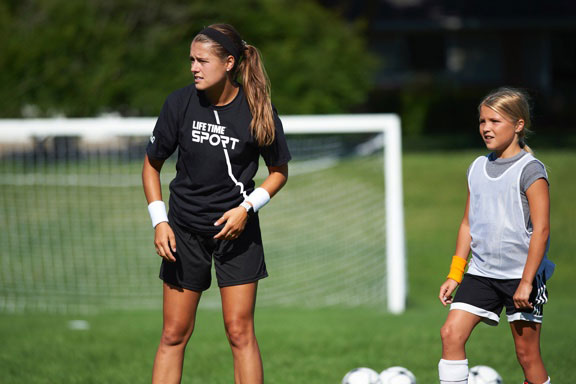Female soccer coach and young female player stand near the goal on outdoor soccer field