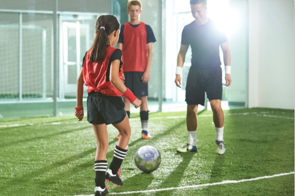 Youth soccer player prepares to kick a soccer ball on indoor soccer field